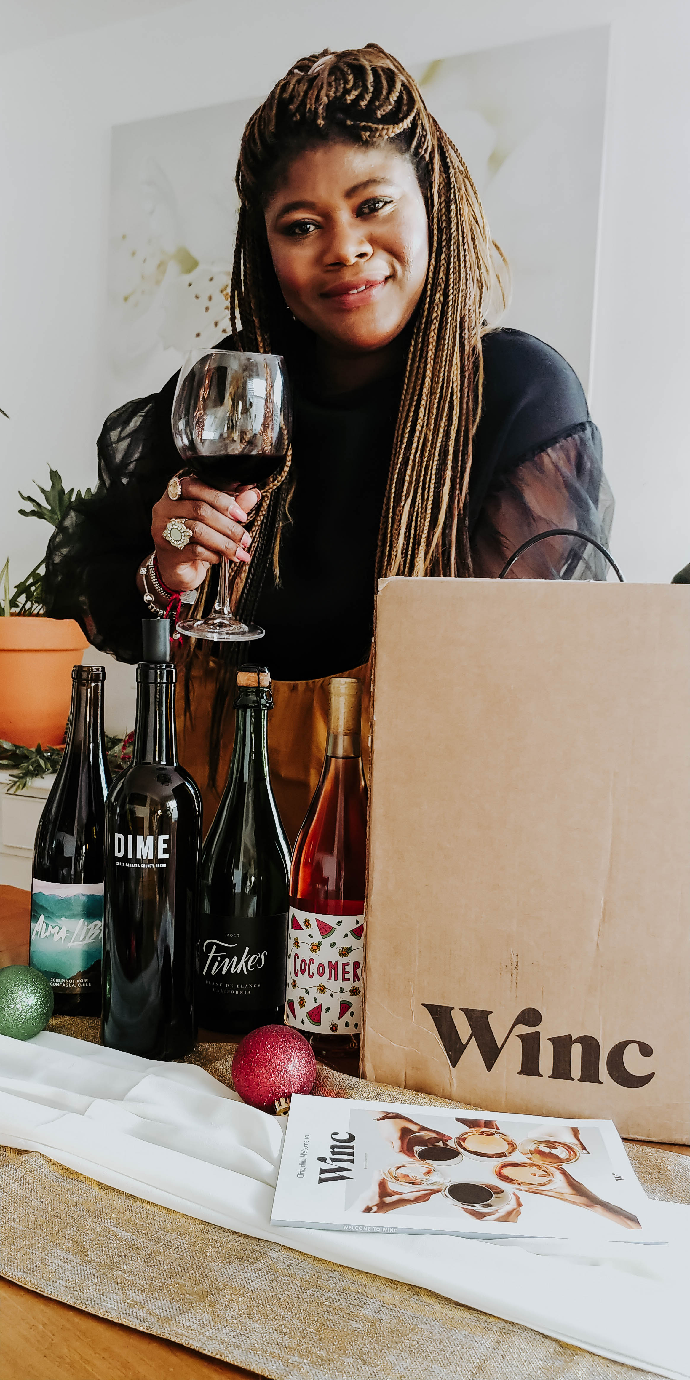 Image of Glory with wine glass and bottles of wine from winc.com.