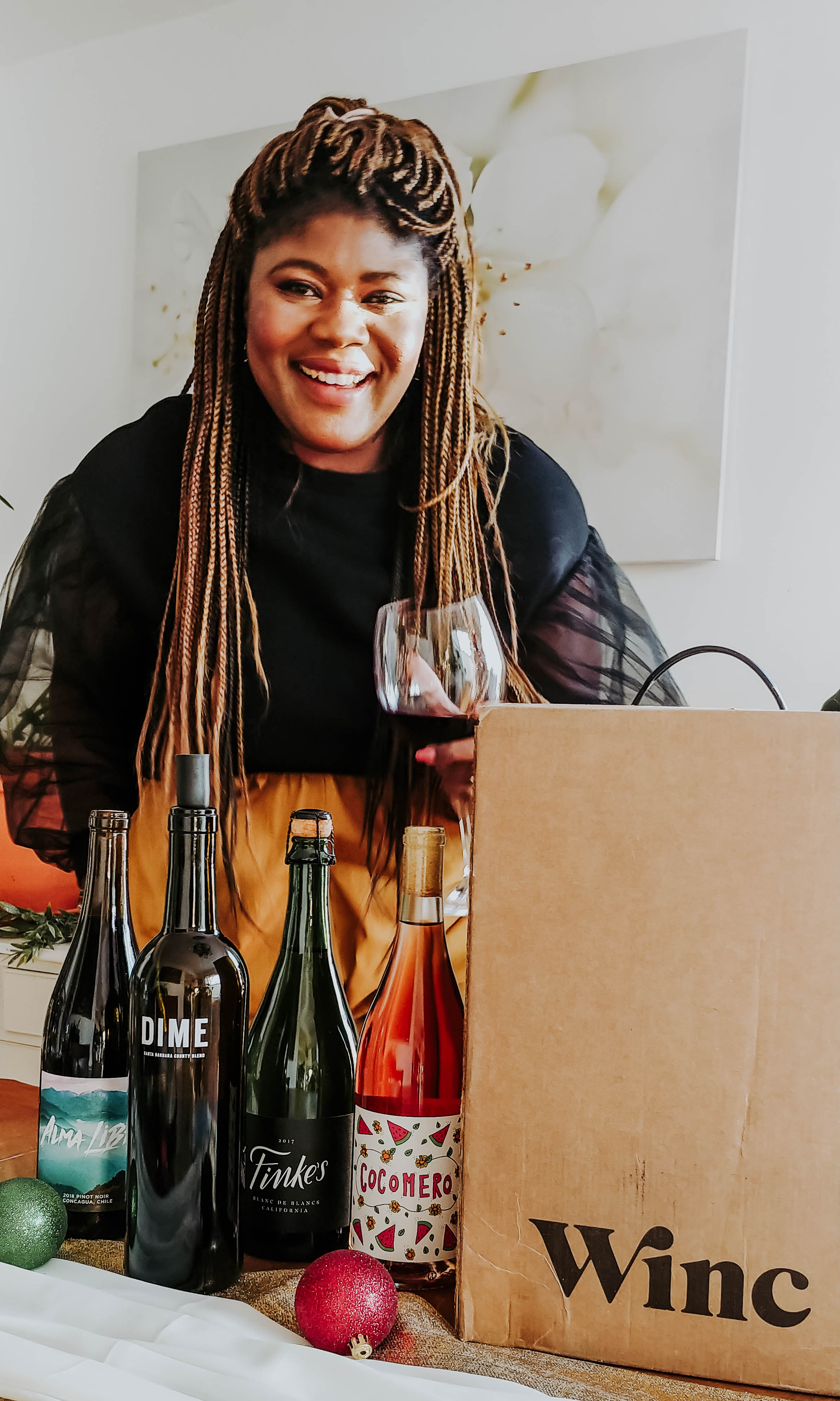 Image of Glory smiling with wine glass in hand and bottles of wine from winc.com.
