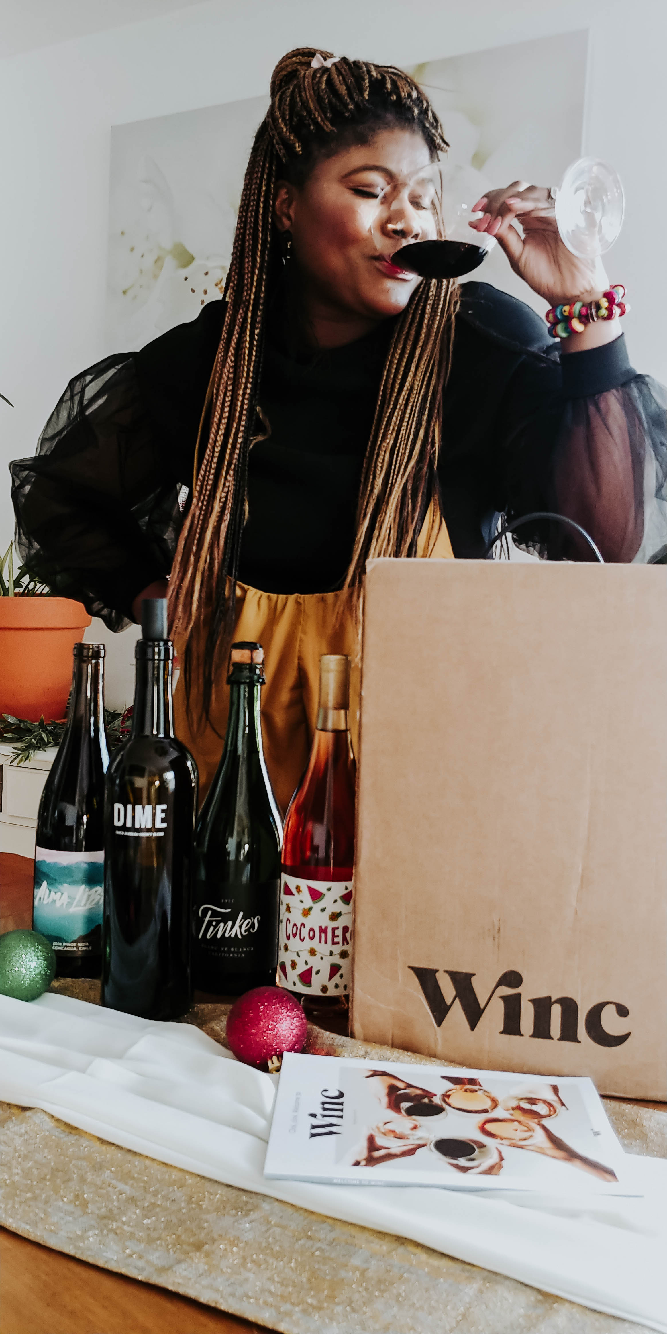 Image of Glory drinking wine and bottles of wine from winc.com.